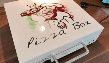 Pizzabox vpn Emerio auf Küchentisch - weißer Aluminiumkasten zum Öffnen mit Aufdruck Pizzabox und ein Cartoon Pizzabäcker