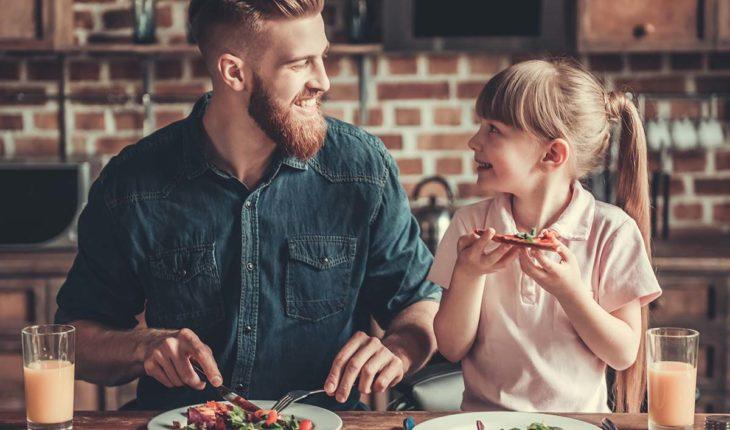 Vater mit Tochter isst eine leckere Pizza am Küchentisch. Mit dem Pizzaofen Alfredo von Bestron geht das ganz einfach.